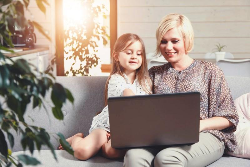 Mutter mit Kind auf dem Sofa am Laptop