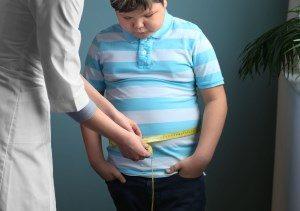 Einem Übergewichtiger Junge wird der Bauchumfang gemessen.