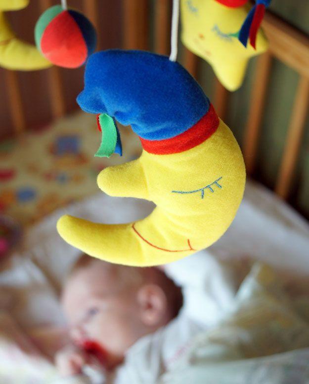 Eine Spieluhr hängt über dem Bett eines schlafenden Kindes