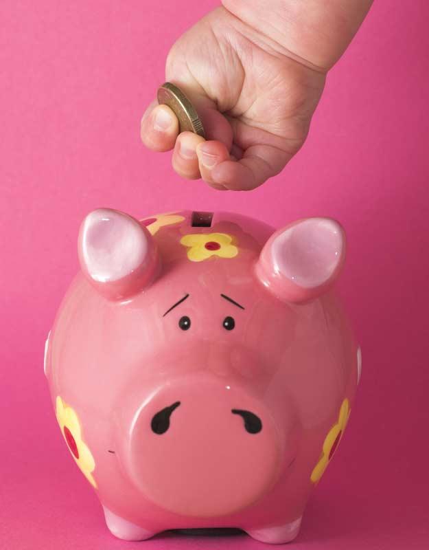Ein kleines Kind wirft ein Geldstück in sein Sparschwein.