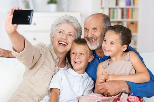 Großeltern mit Enkeln auf der Couch fotografieren mit dem Smartphone