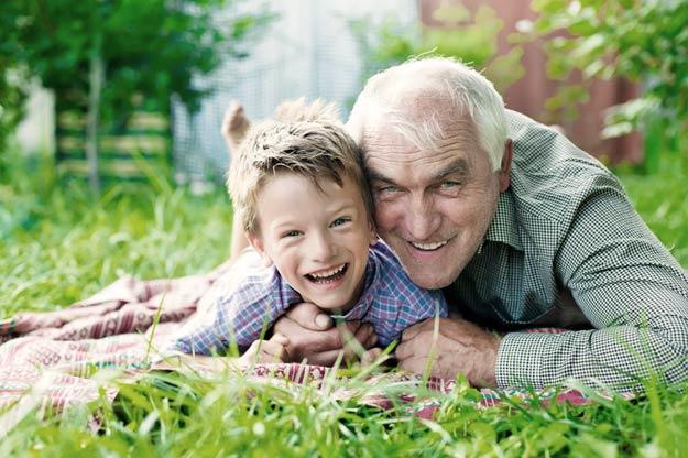 Großvater mit Enkelsohn liegend auf einem grünen Rasen
