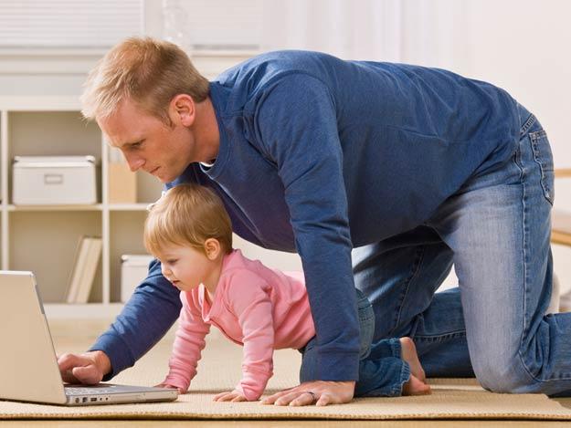 Vater spielt mit seiner Tochter am Laptop