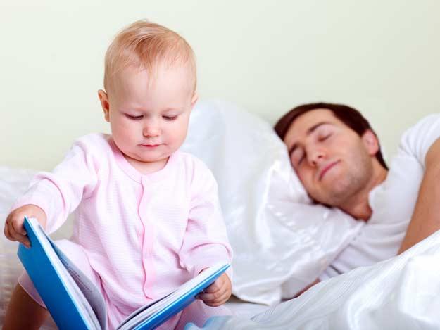 Ein kleines Kind mit einem Buch neben seinem schlafenden Vater.