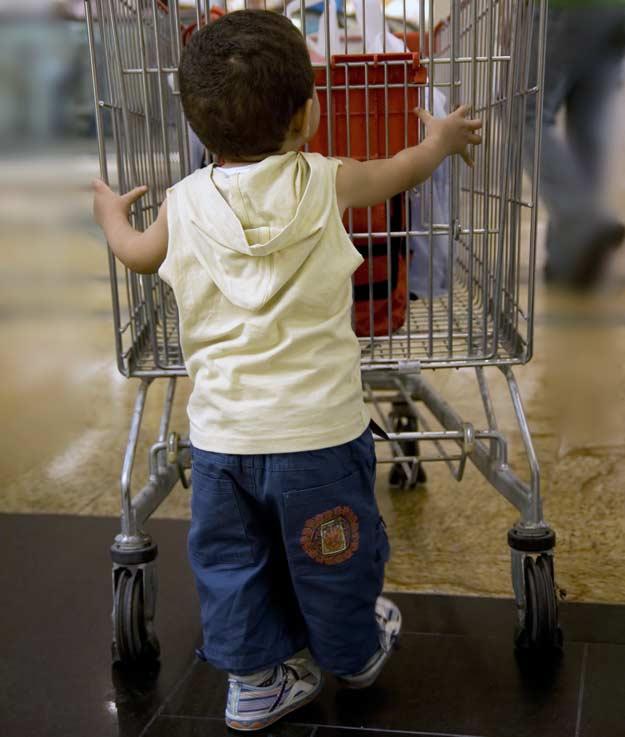 Ein kleiner Junge schiebt einen Einkaufswagen.