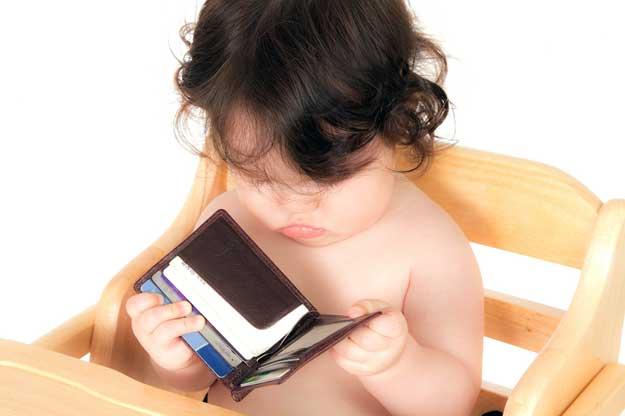 Ein kleines Kind prüft den Inhalt eines Geldbeutels.