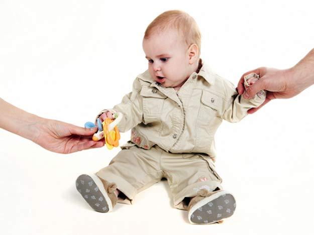 Ein Baby zwischen den Händen von Vater und Mutter.