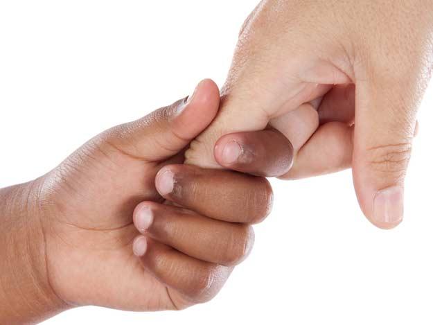 Kind hält den Finger eines Erwachsenen