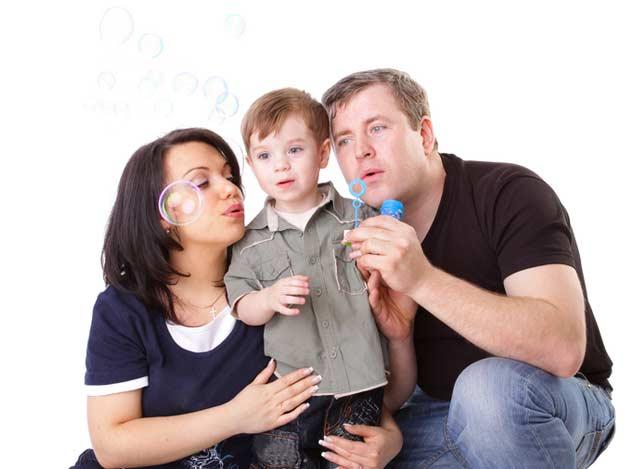 Eltern mit Kind machen Seifenblasen