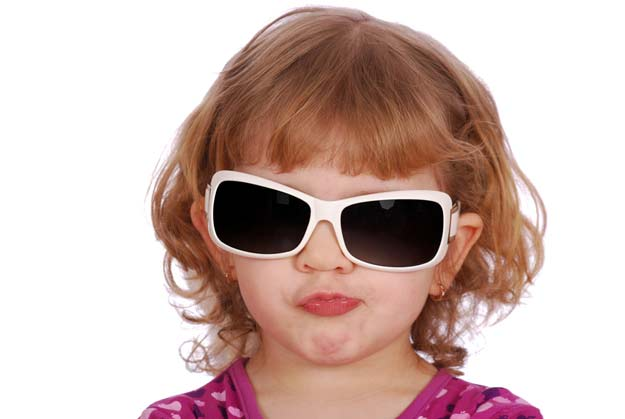 Ein Kind schützt seine Augen mit einer Sonnenbrille.