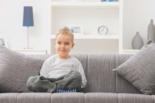 Ein Junge sitzt auf der Couch.
