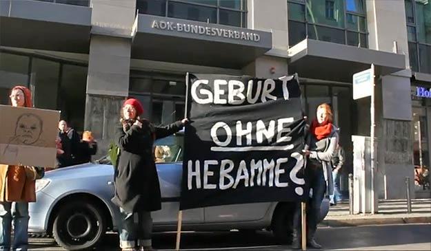Zwei Frauen halten ein schwarzes Plakat hoch
