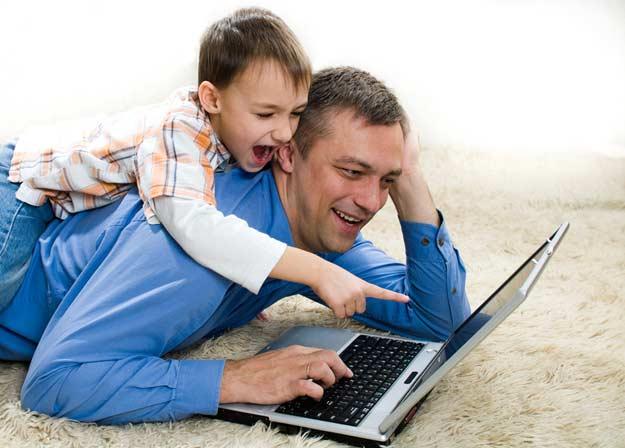 Kind, das zurück auf seinem mit seinem Vater liegt mit Laptop