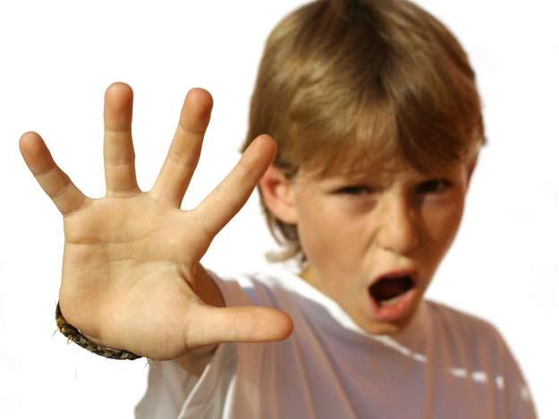 Ein Kind hält die Hand schützend vor seinen Körper.