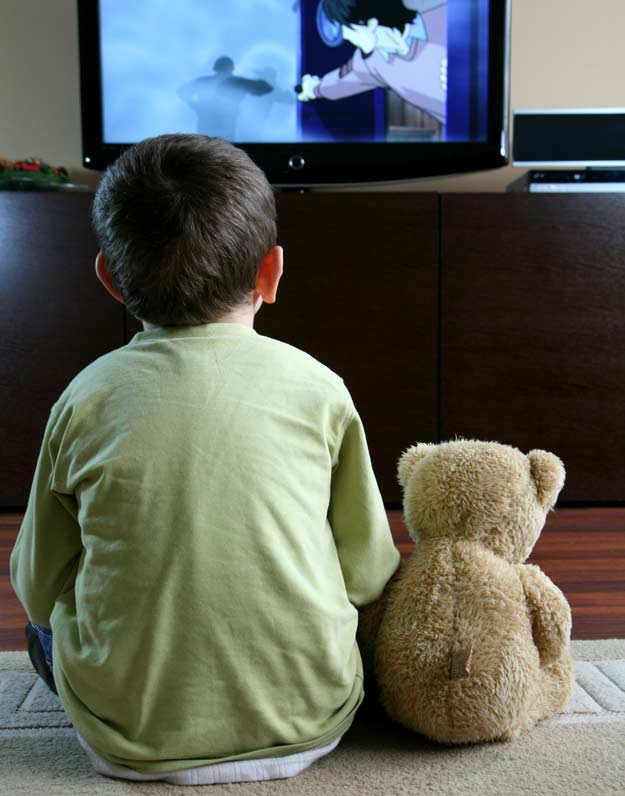 Ein Kind sitzt vor dem Fernseher.