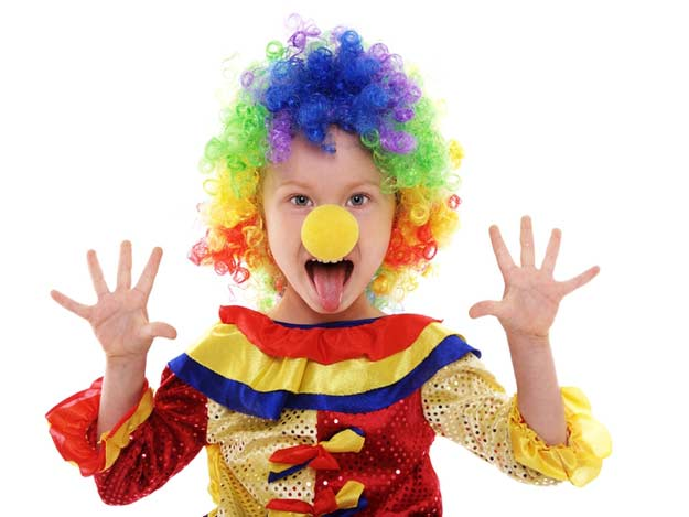 Ein Junge hat sich als Zirkusclown verkleidet.