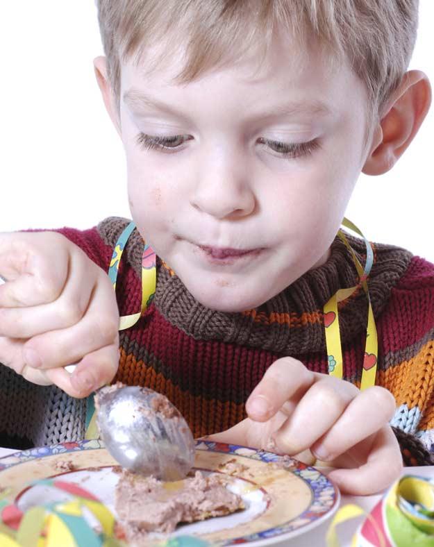 Ein Junge isst Maulwurfkuchen.
