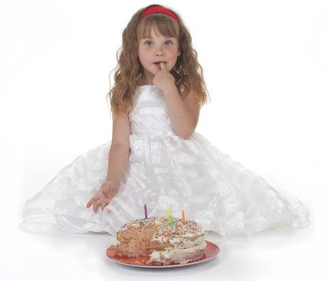 Vier Einjahresmädchen im weißen Partykleid mit Geburtstagkuche