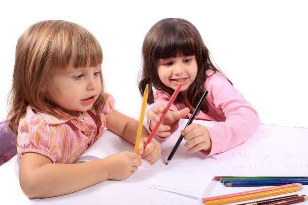 Zwei kleine Mädchen beschäftigen sich mit Buntstiften und einem Blatt Papier.