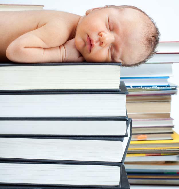 Ein Baby liegt auf einem Stapel Bücher.