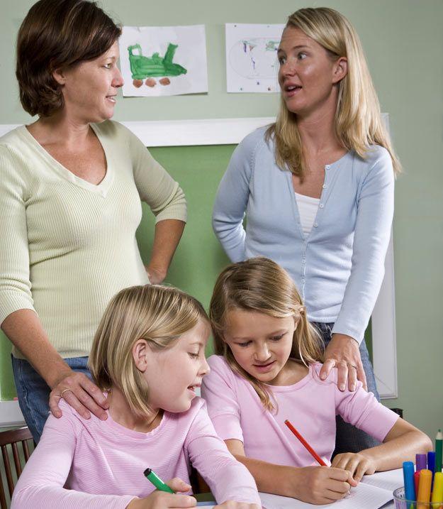 Schülerinnen, Lehrerin und Mutter im Klassenzimmer.