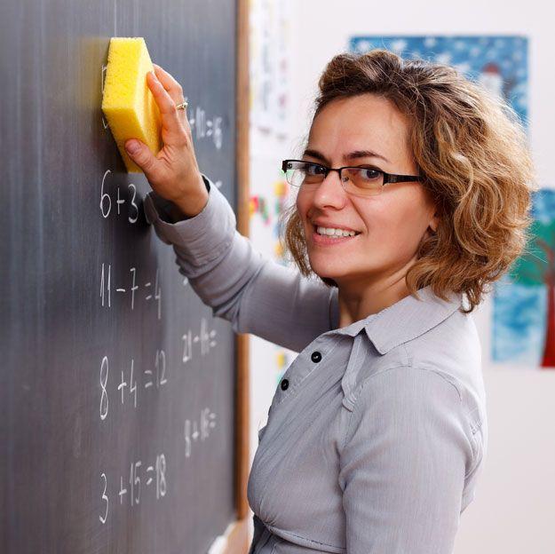 Eine Lehrerin wischt die Tafel mit einem Schwamm ab.