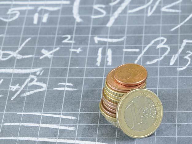 Mathematische Formeln auf einer Schultafel und Geldmünzen.
