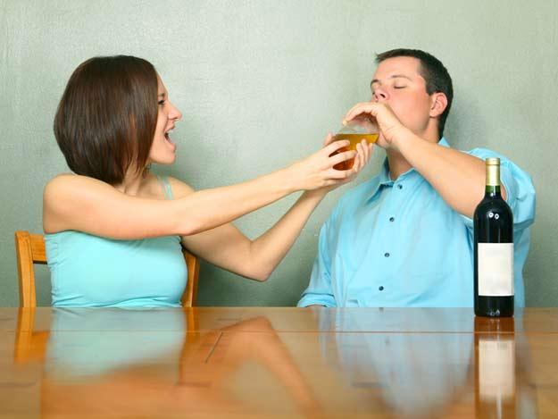 Eine Frau nimmt ihrem Partner die Flasche weg.