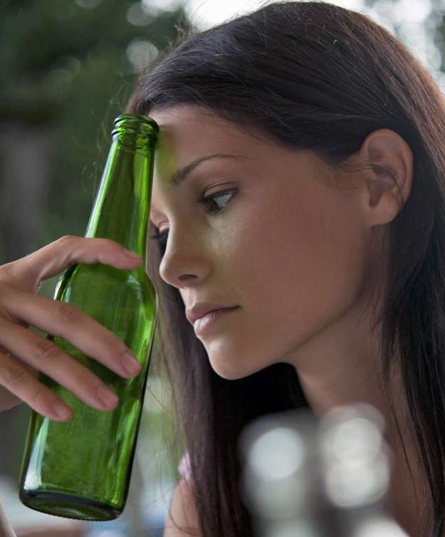 Junge Frau mit Weinflasche