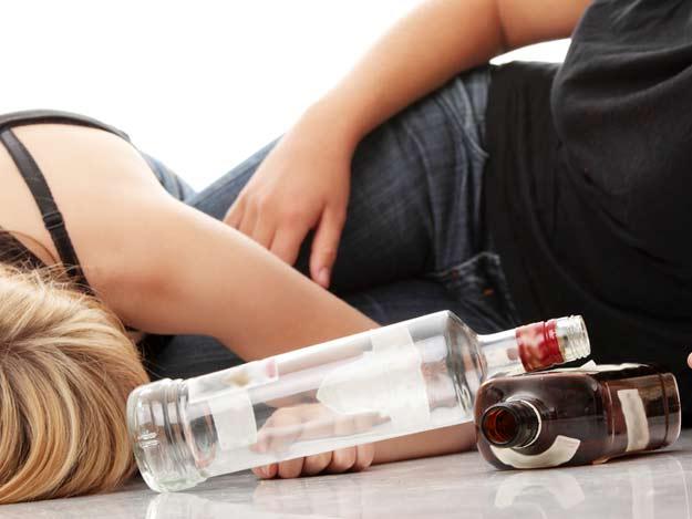 Betrunkene Jugendliche mit leeren Schnapsflaschen.