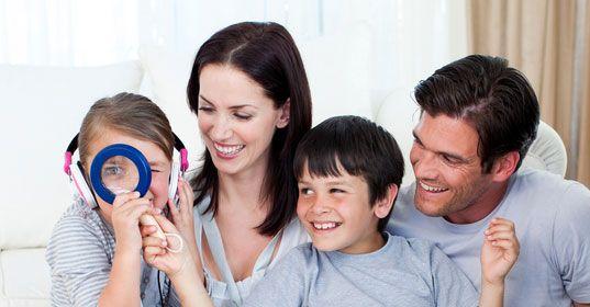 Glückliche Familie, die mit einem Vergrößerungsglas spielt
