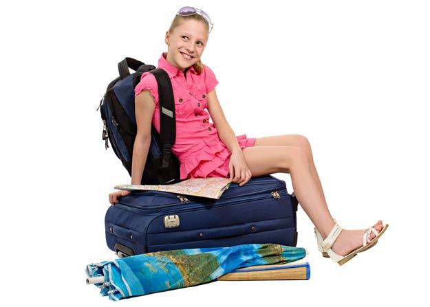 Mädchen sitzt auf gepackten Koffer