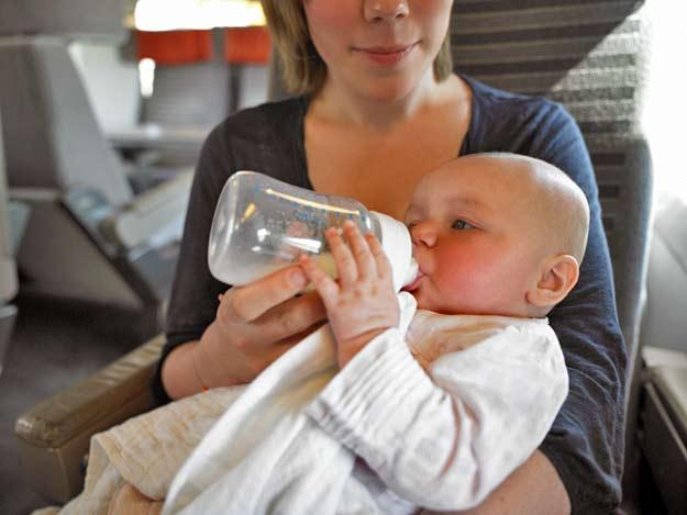 Eine Mutter füttert ihr Kind an Bord eines Flugzeuges.