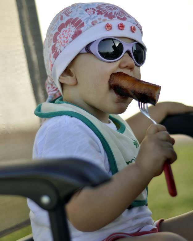 Ein Kind isst eine frisch gegrillte Wurst.