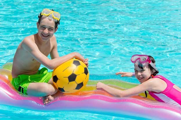 Kinder die im Pool mit Wasserspielzeug spielen