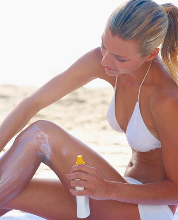 Eine junge Frau am Strand versorgt ihre Haut mit Sonnenschutzcreme.