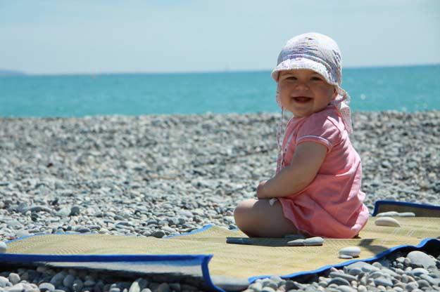 Ein Baby beim Sonnenbaden am Strand.