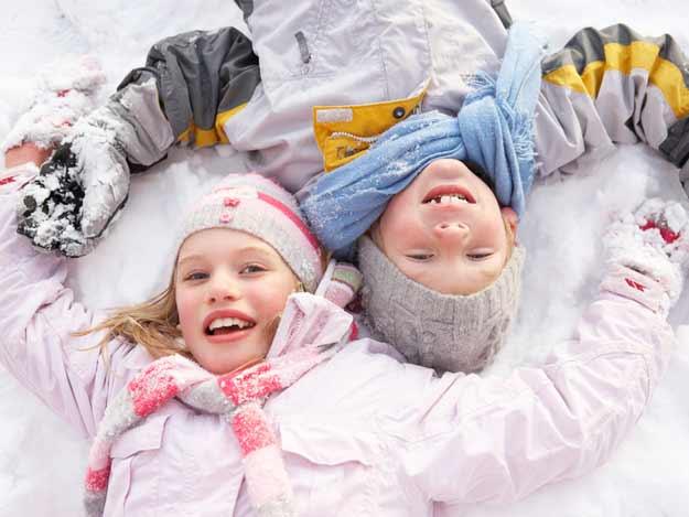 Junge und Mädchen liegen im Schnee