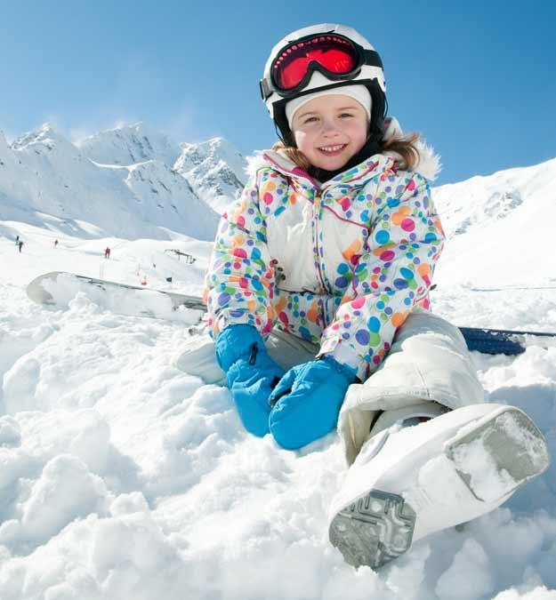 Mädchen sitzt in Skiausrüstung im Schnee